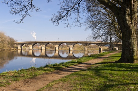 Hexham Bridge and riverside path from upstream framed by trees Stock Photo - 13055811