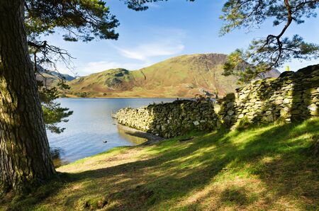 Stone wall into Crummock Water in the English Lake District National Park Stock Photo - 16313145