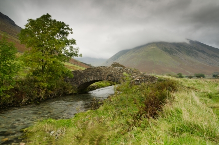 Stone bridge near Wastdale Head with mountain stream flowing below on a stormy day in the Lake District National Park Stock Photo - 16313140
