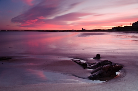 Red sunset at Blyth beach reflected from the wet sand and sea Stock Photo