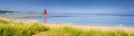 South Shields Beach panorama with the the Groyne Lighthouse sitting in the mouth of the River Tyne to protect the beach and help with navigation