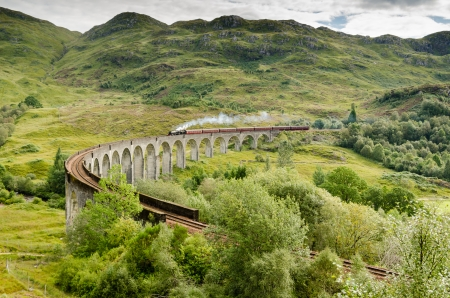 The famous Glenfinnan Viaduct with steam train which carries it from Fort William to Mallaig Stockfoto