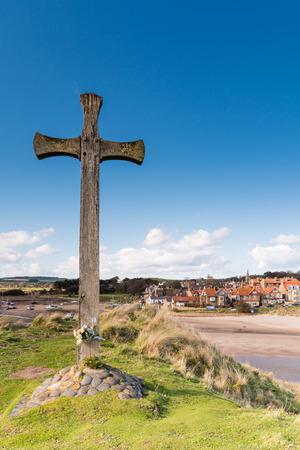 diverted: Wooden Cross at Alnmouth on Church Hill marking the spot where the village church stood until a storm diverted the River Aln cutting it off Stock Photo