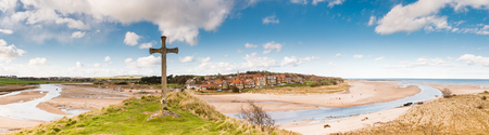 diverted: Alnmouth Village panorama with the wooden cross on Church Hill marking the spot where the village church stood until a storm diverted the River Aln cutting it off Stock Photo