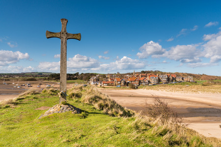 Alnmouth Village and wooden cross on Church Hill which marks the spot where the village church stood until a storm diverted the River Aln cutting it off photo