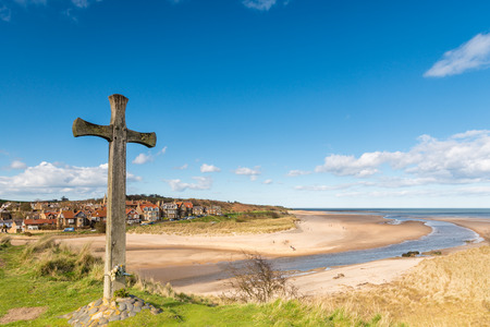 diverted: Alnmouth beach with Wooden Cross on Church Hill marks the spot where the village church stood until a storm diverted the River Aln cutting it off