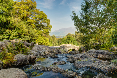 Ashness Packhorse Bridge with Derwent Water, Keswick and Mount Skiddaw beyond is an old single track packhorse bridge photo