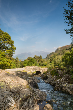 Ashness Bridge vertical with Derwent Water, Keswick and Mount Skiddaw beyond is an old single track packhorse bridge photo