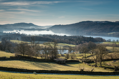 Morning mist over Windermere Lake  Windermere is the largest natural lake in England viewed here with morning mist rising in winter photo