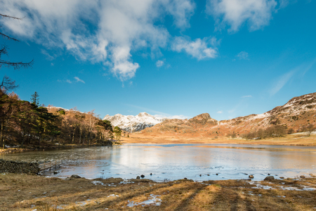 fells: Blea Tarn with snow covered Side Pike  Blea Tarn is a remote  small lake among the Langdale Fells in the Lake District