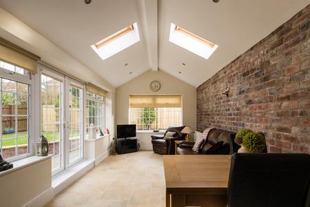case moderne: Sun Room  Modern veranda o giardino d'inverno che si estende in giardino con un muro di mattoni in evidenza Archivio Fotografico