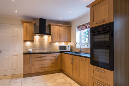 Domestic Kitchen / Modern domestic kitchen with a light oak shaker style design and tiled floor and backsplash