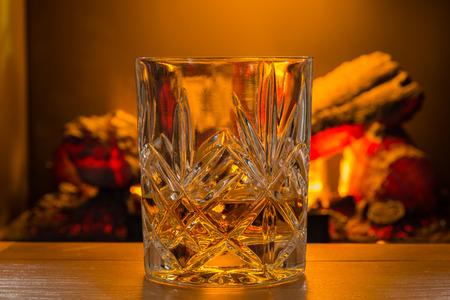 log fire: Scotch Whisky in vetro  Whiskey in un bicchiere di cristallo tagliato retroilluminato da un caminetto defocussed per dare una sensazione di calore