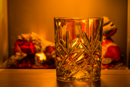 log fire: Whiskey in glass  Whiskey in a cut crystal glass backlit by a defocussed log fire to give a feeling of warmth
