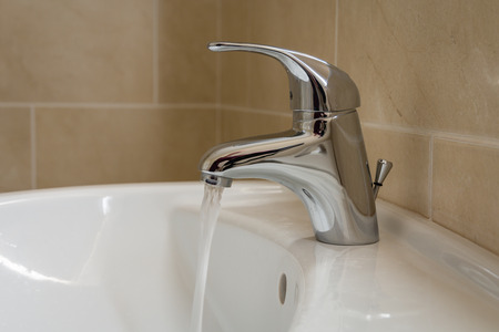 Bathroom sink tap with running water  Single lever monobloc chrome mixer tap on bathroom sink Stock Photo