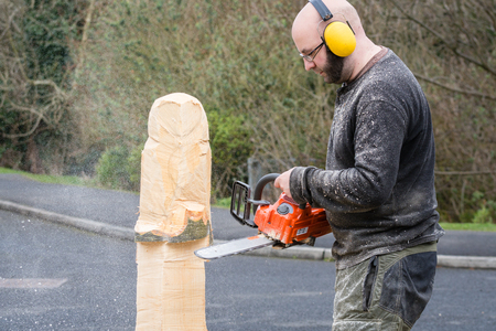Chainsaw sculptor  The making of an owl sculpture by a chainsaw sculptor here in the early stages photo