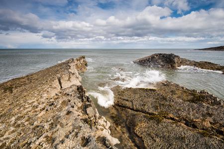 howick: Sea meets rock at Howick Coastline  The sea crashing into rocks causing waves and spray on the Northumberland coastline near Howick Stock Photo