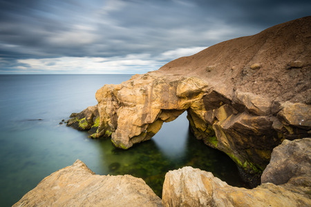 Saddle Rocks in smooth water  Saddle Rocks at Cullercoats Whitley Bay here at high tide using a long exposure to blur the water and clouds Stock fotó