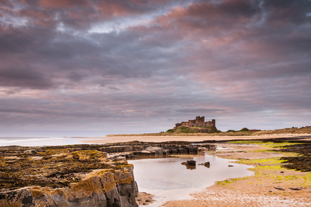 leading light: Bamburgh Castle after dawn  Rocks leading to Bamburgh Castle from the beach at low tide in the warm light after sunrise Editorial