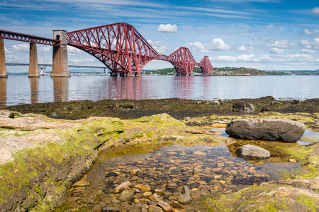 bridge: Forth Bridge at low tide  The famous Forth Cantilever Railway Bridge spans the Firth of Forth on a sunny day with a rock pool in the foreground