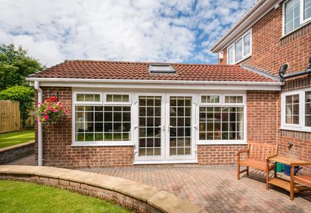 ブロック舗装されたテラスに囲まれた近代的なサンルーム コンサバトリー - 現代 Sunroom または温室、庭園に拡張