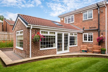 Modern Sunroom external - Modern Sunroom or conservatory extending into the garden, surrounded by a block paved patio Stock Photo - 42659569