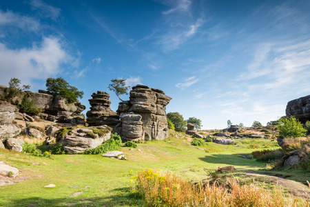 boulder rock: Brimham Rocks on a sunny day - Brimham Rocks on Brimham Moor in North Yorkshire are weathered sandstone, known as Millstone Grit,creating some dramatic shapes, many of which have been named Stock Photo