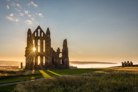Whitby 수도원에 태양 별 Whitby 수도원의 고딕 유적 별을 생산하는 태양 광선. 백그라운드에서 Sandsend의 절벽에서 뒤로 물러나는 바다 안개