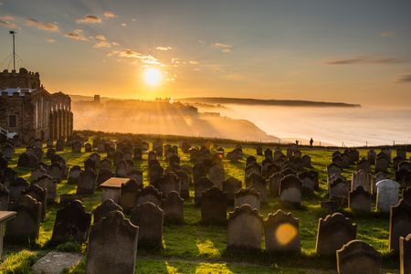 whitby: Church of St Mary Graveyard Sunset  The low sun shines through the sea mist creating an atmospheric scene on the Church of St Marys graveyard in Whitby