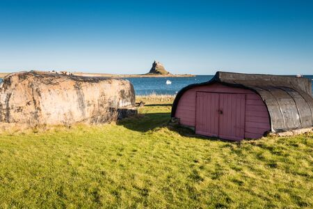 upturned: Lindisfarne Boats and Castle - Upturned boat hulls used for storage sheds on Holy Island, with Lindisfarne Castle behind Editorial