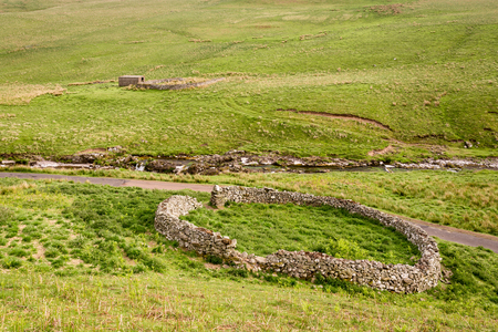 sheepfold: Sheepfold in Upper Coquetdale - The River Coquet winds its way through Upper Coquetdale Valley past many circular sheepfolds, protection in the harsh winters Stock Photo