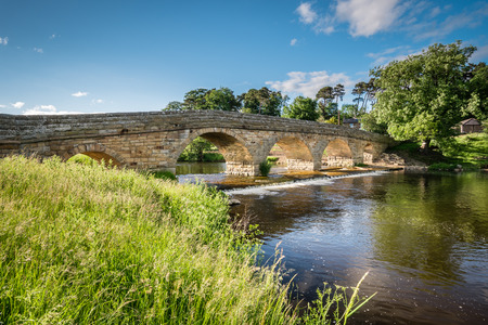 downstream: Pauperhaugh Bridge and Weir - Pauperhaugh Bridge just downstream from Rothbury town, on the River Coquet in Northumberland Stock Photo