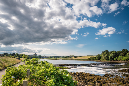 riverbank: Weir on River Coquet below Warkworth Village, with the castle on the skyline Stock Photo