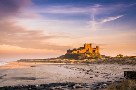 Golden Bamburgh Castle - Bamburgh Castle on the Northumberland coastline, bathed in late afternoon golden sunlight