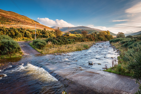 Ford on College Burn and The Cheviot, from which the hill range takes its name, and is the highest point in Northumberland, located in the Anglo-Scottish borders, seen here in autumn from College Valley Stock Photo