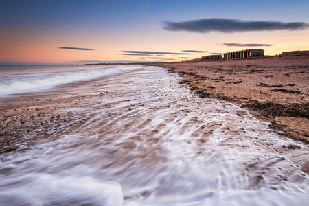Blyth Beach retreating waves, as the Blyth Beach Huts overlook the North Sea, in twilight