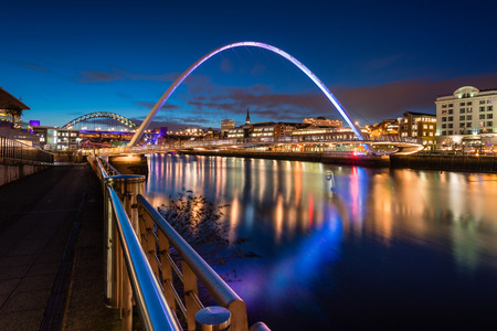 Twilight at Gateshead Millennium Bridge, at the Quayside in Newcastle, on the banks of the River Tyne, and Newcastle upon Tyne skyline beyond