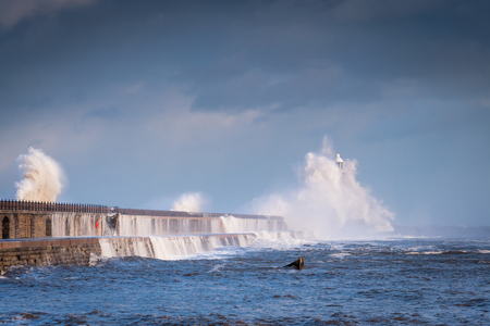 Tynemouth Lighthouse engulfed by Waves, as a stormy sea hits Tynemouth North Pier, resulting in high crashing waves cascading into the mouth of the River Tyne Stock Photo