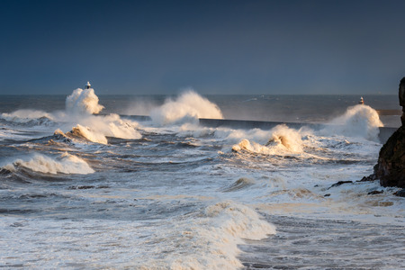 Surging Waves onto Tynemouth Pier, in a stormy sea, resulting in high crashing waves cascading into the mouth of the River Tyne