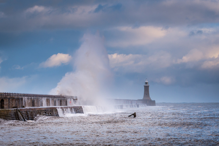 Storm Surge at Tynemouth Pier, as a stormy sea hits it, resulting in high crashing waves cascading into the mouth of the River Tyne Stock Photo