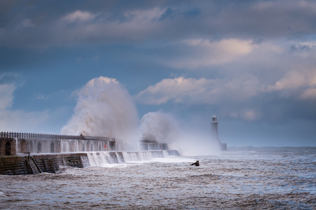 Cascading Waves over Tynemouth Pier, as a stormy sea hits it, resulting in high crashing waves cascading into the mouth of the River Tyne