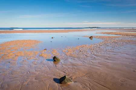 Shipwreck remains on Bamburgh Beach - On Bamburgh Beach at low tide just below Bamburgh Castle, lies an unknown wooden shipwreck, overlooked by the Farne Islands on the horizon Stock Photo