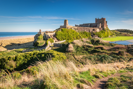 Elevated View of Bamburgh Castle - Bamburgh Castle viewed from an elevated hillock, on the Northumberland coastline Stock Photo