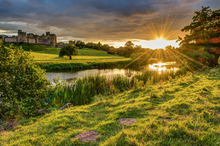 Sunbeams over River Aln at Alnwick, which runs through Northumberland from Alnham to Alnmouth. Seen here below Alnwick Town and Castle on the skyline, as the sun goes down 免版税图像