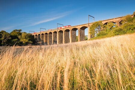 Lesbury Viaduct with Train, with a motion blurred train and hay, passing over the River Aln as it approaches the North Sea at Alnmouth
