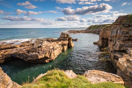 ハウィック ノーサンバーランドの海岸線の近くのゴロゴロのカーンで岩の入り江にある小さなビーチと小さな崖に入り江