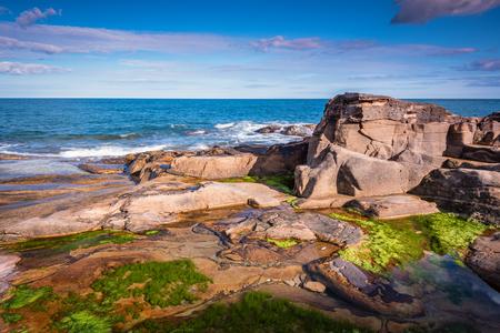 小さなビーチと小さな崖に入り江にあるハウィック ノーサンバーランド海岸に近く、カーン ロックプールをゴロゴロ 写真素材