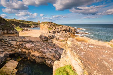 岩の入り江とハウィック ノーサンバーランドの海岸線の近くのゴロゴロのカーンでビーチにある小さなビーチと小さな崖に入り江 写真素材