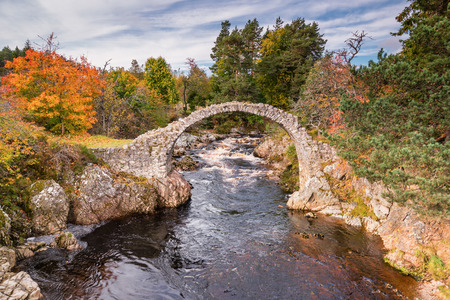 Carrbridge Packhorse Bridge in Autumn, one of the most iconic visitor attractions in the Cairngorms, the old packhorse bridge across the River Dulnain at Carrbridge