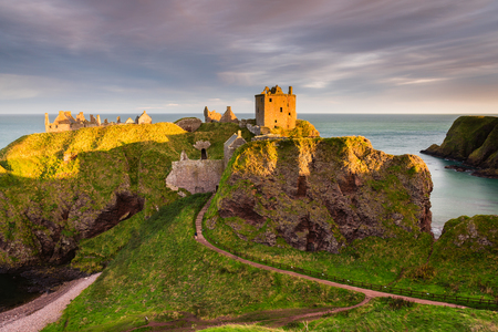 Golden Light on Dunnottar Castle, a ruined medieval fortress located upon a rocky headland on the north east coast of Scotland, near Stonehaven Stock Photo